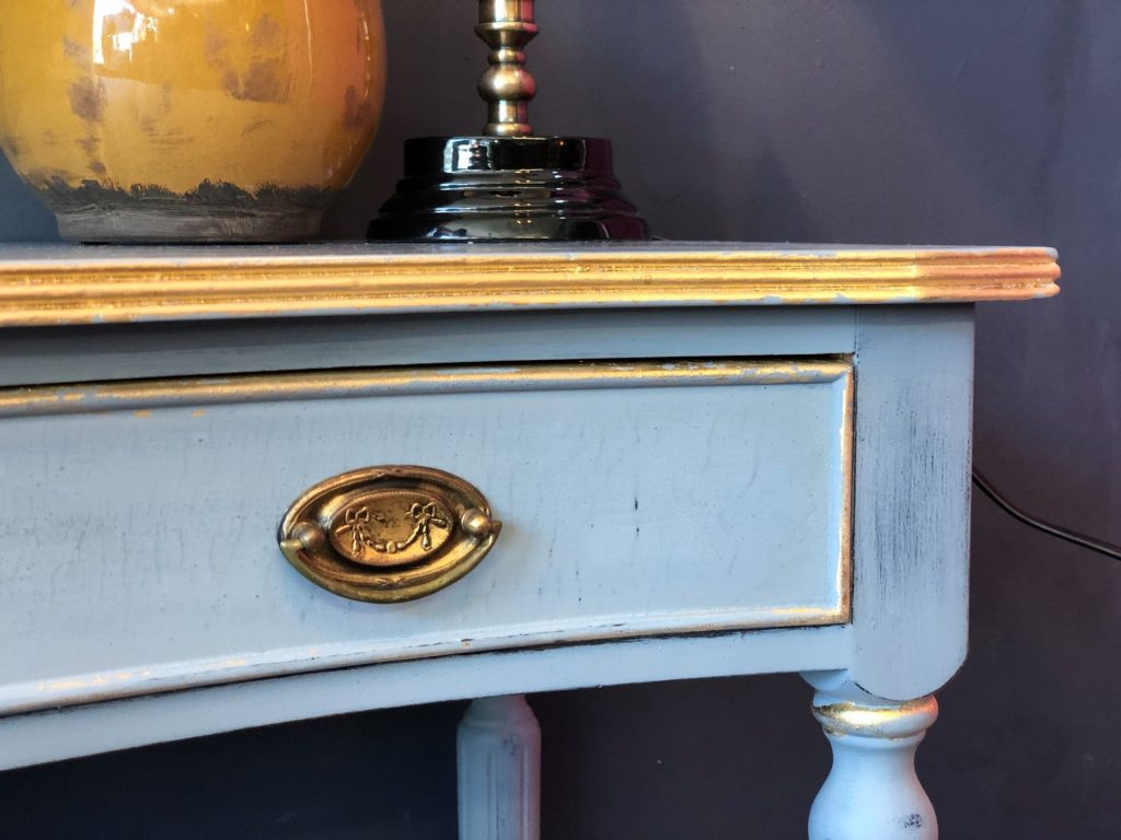 worn soft blue paint over navy, a touch of gold leaf peeking through.