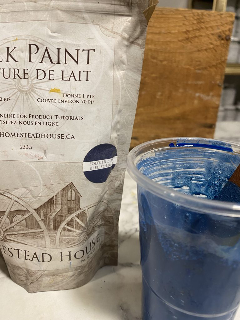 Packet of Homestead House Solider Blue Milk Paint and a cup with mixed milk paint.