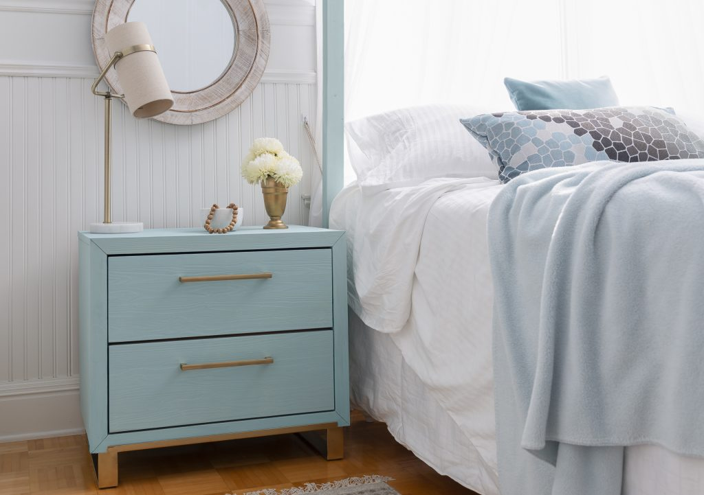 A small bedside table painted in a soft aqua blue with gold hardware and legs. Bedroom scene