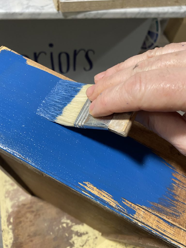 Blue paint being brushed on drawer front