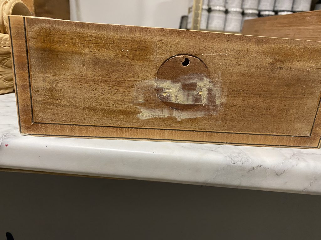 A drawer front sanded and filled with wood filler