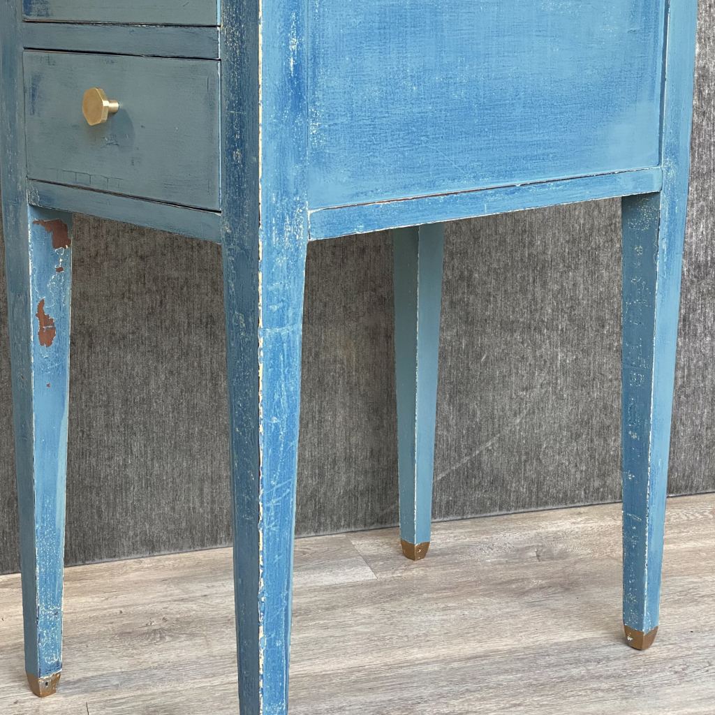 side view of bedside table painted in chippy layered milk paint finish