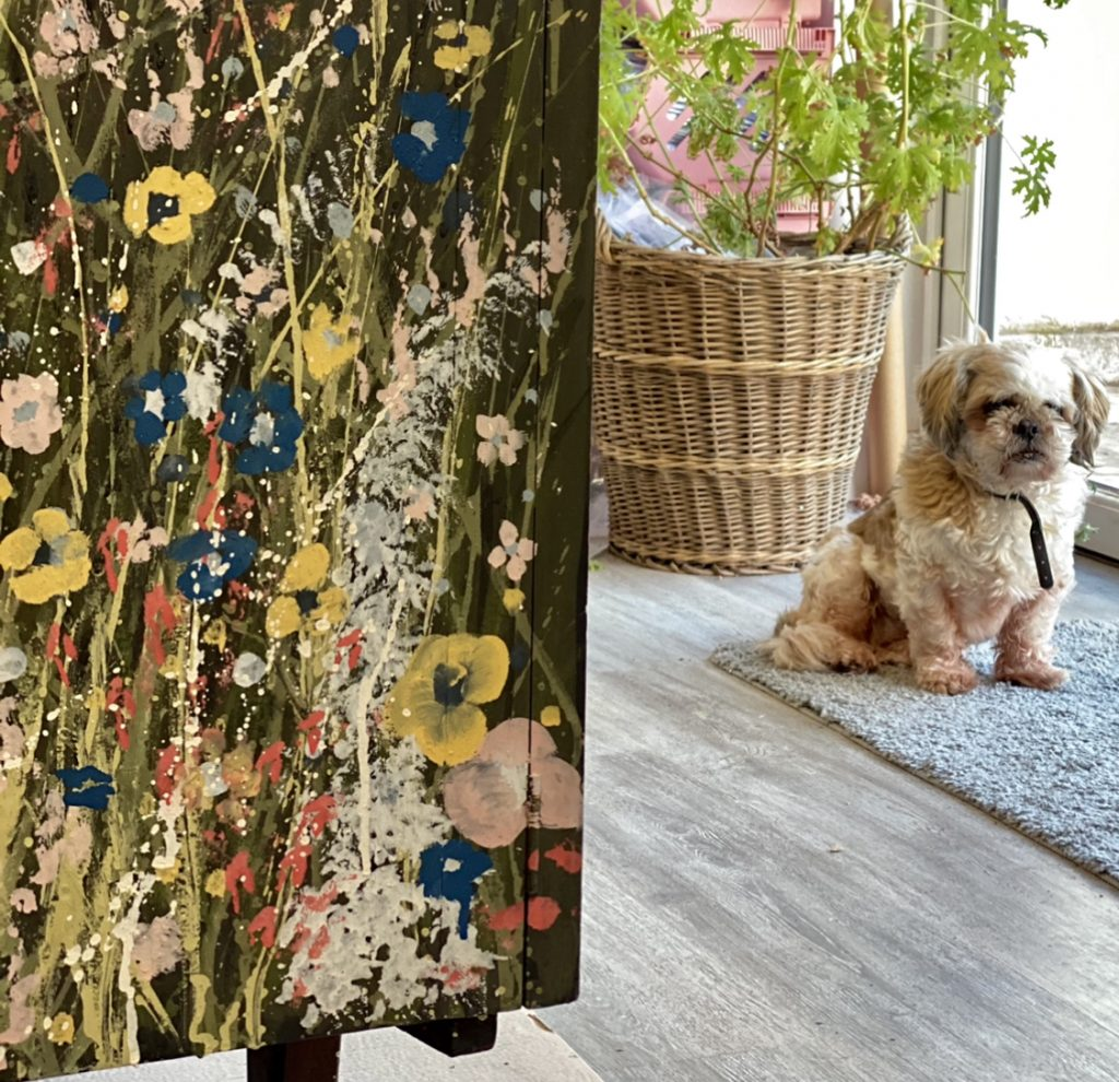 corner of painted flowers on  sideboard and dog in the background with plant